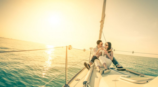 Young couple in love on sail boat with champagne at sunset - Happy exclusive alternative lifestye concept  - Soft focus due to backlight on vintage nostalgic filter - Fisheye lens and tilted horizon